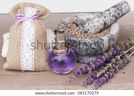 Lavender herbal water in a glass bottle with fresh and dry flowers on  table - stock photo
