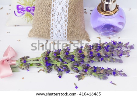 Lavender herbal water with fresh and dry flowers on white wood - stock photo
