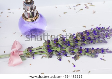 Lavender herbal water with fresh  flowers on white wooden table - stock photo