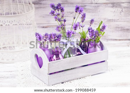 Lavender in bottles, decor provance style, wooden box and birdcage on crochet tablecloth - stock photo