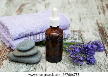 Lavender, oil and towels on a wooden background - stock photo