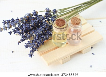 Lavender oil and water in bottles with bunch of herbs - stock photo