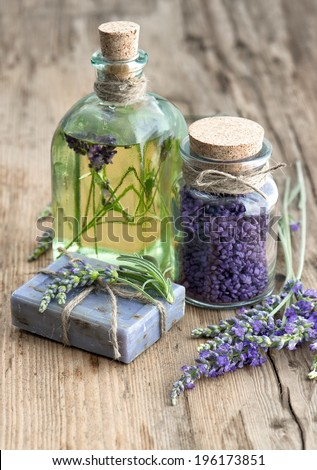 lavender oil, herbal soap and bath salt with fresh flowers on wooden background - stock photo