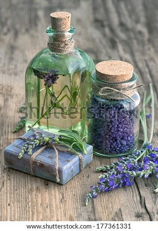 lavender oil, herbal soap and bath salt with fresh flowers on wooden background. vintage style toned picture - stock photo