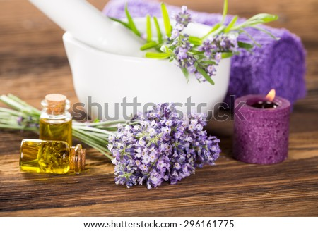 Lavender oil, herbal towel and fresh lavender flowers on wooden background. Wellness still-life. - stock photo