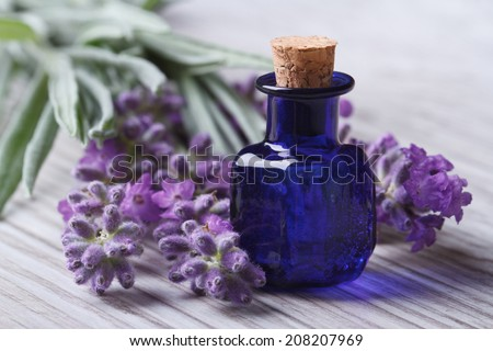 lavender oil in a blue glass bottle and flowers on the table. horizontal macro  - stock photo