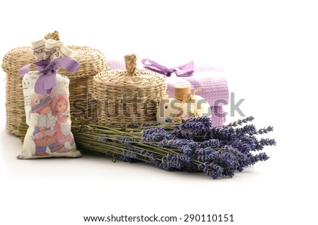 Lavender oil in a ceramic bottle on a white background of fresh flowers and  baskets - stock photo