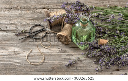 Lavender oil with fresh flowers and scissors on wooden background. Vintage style colored picture. Selective focus - stock photo