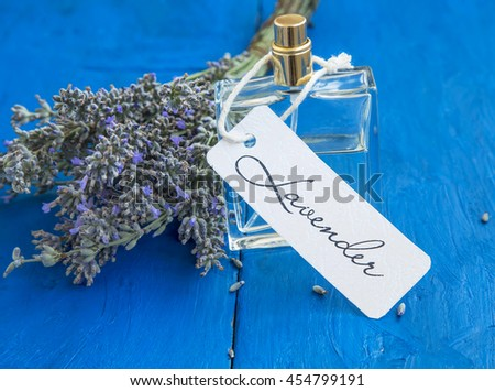 Lavender perfume bottle with label and lavender flowers bunch - stock photo