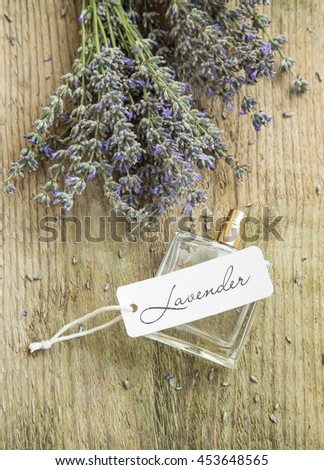 Lavender perfume in a bottle with lavender flowers and label on wooden rustic background - stock photo