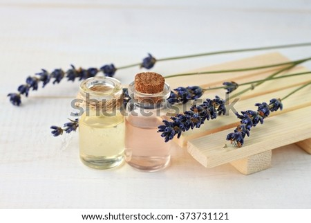 Lavender relaxing remedy. Aroma water and oil in bottles with lavender twigs. - stock photo