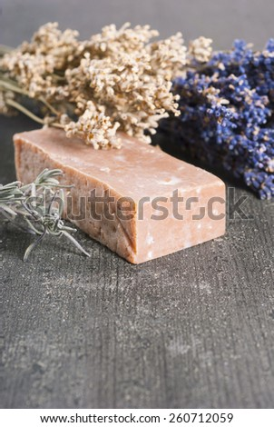 lavender soap and flower on rusty black wood