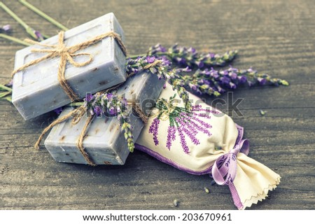 lavender soap and scented sachets with fresh flowers over wooden background. selective focus - stock photo