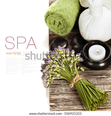lavender spa (fresh lavender flowers,candlel, zen stones,  Herbal massage balls, towel) on a wooden bord  (with easy removable text) - stock photo