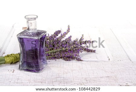 Lavender spa still life with bottle of lavender infused oil on a vintage door - stock photo