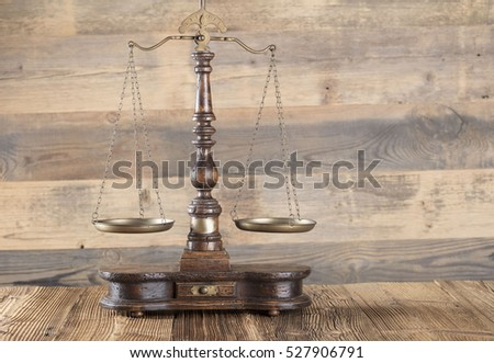Law. Antique scales of justice on a wooden table. Gray background. Place for typography and logo.