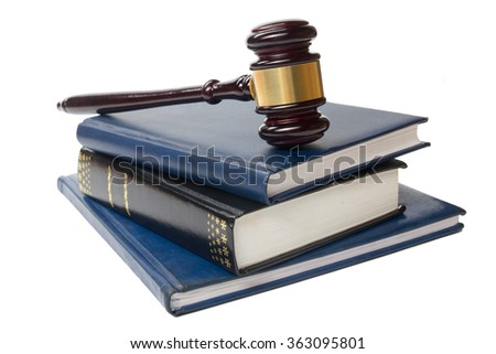 Law book with a wooden judges gavel on table in courtroom  - stock photo
