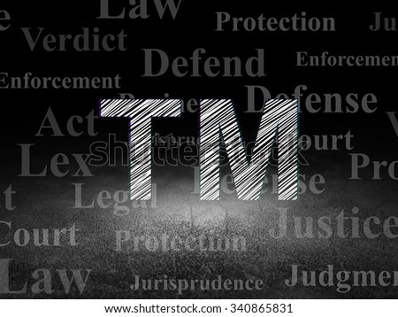 Law concept: Glowing Trademark icon in grunge dark room with Dirty Floor, black background with  Tag Cloud - stock photo