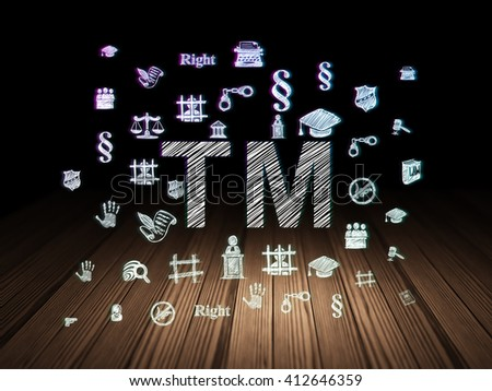 Law concept: Glowing Trademark icon in grunge dark room with Wooden Floor, black background with  Hand Drawn Law Icons - stock photo