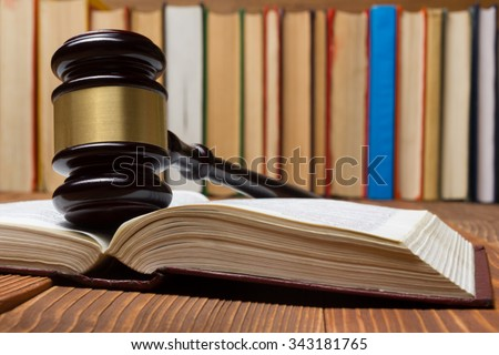 Law concept - Law book with a wooden judges gavel on table in a courtroom or law enforcement office. - stock photo