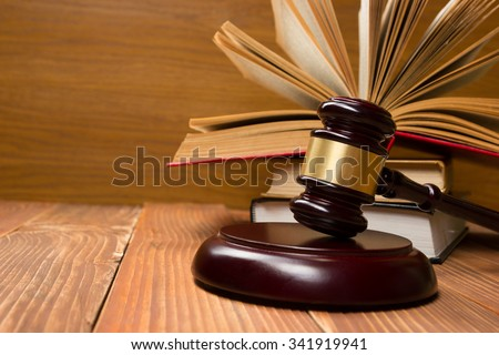 Law concept - Open law book with a wooden judges gavel on table in a courtroom or law enforcement office. Copy space for text