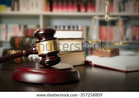 Law concept with gavel and scale in background. Composition in court library - stock photo