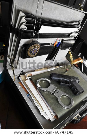 Law enforcement tools of the trade, briefcase, paperwork, handcuffs, firearm, and badge/Law & Order - stock photo