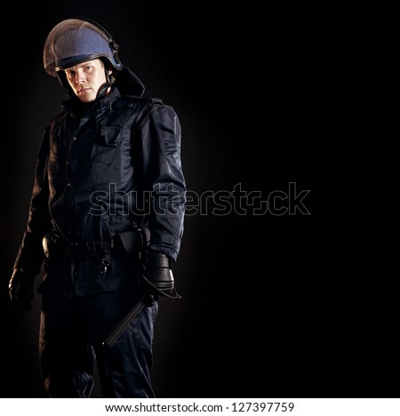 Law enforcer in protective uniform ready for crowd control isolated on black - stock photo