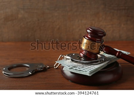 Law gavel with dollars and handcuffs on wooden table background, closeup - stock photo