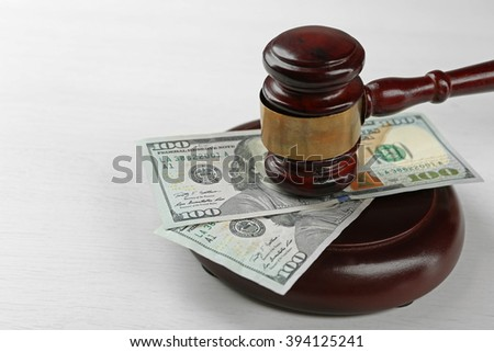 Law gavel with dollars isolated on white - stock photo