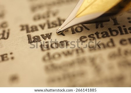 Law pen nib pointing to the words in the dictionary, shot with very shallow depth of field, - stock photo