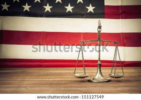 Law scales on table front of USA flag. Symbol of justice. Retro style photo - stock photo