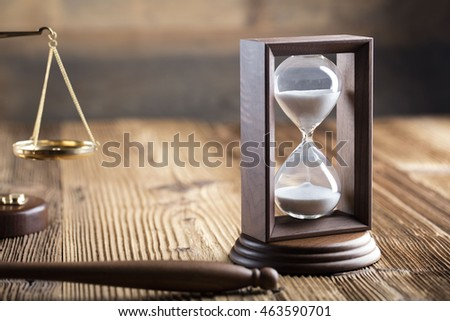 law theme, mallet of the judge, wooden desk, scales of justice, books, statue of justice and hourglass