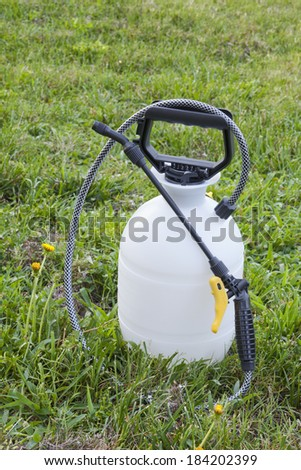 Lawn and garden sprayer for dispensing fertilizer, pesticide or herbicide sitting in grass among dandelions. - stock photo