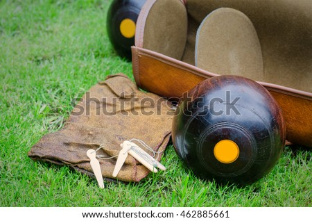 Lawn Bowls. Two wooden bowling balls on freshly cut grass with measuring device, leather bag and cloth.
