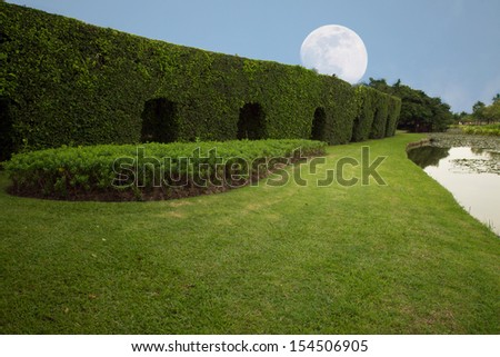Lawn by the pool in landscaped gardens, peaceful moonlight.  - stock photo