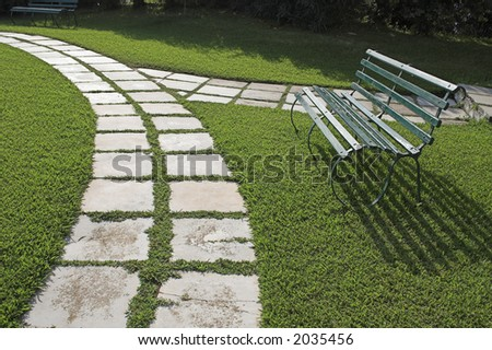 Lawn chairs on green grass in garden with curved walkway