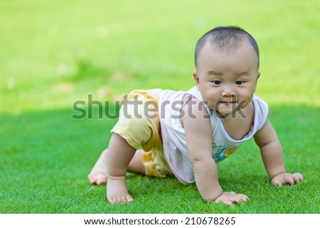Lawn crawling baby in the park - stock photo