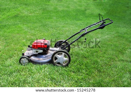 Lawn mower against on green grass background - stock photo