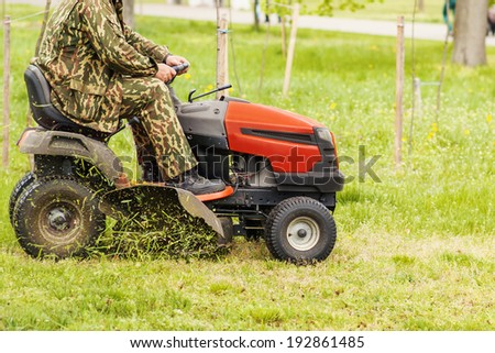 Lawn mower and a man on a green field - stock photo