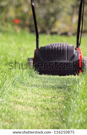 Lawn-mower cuts a high green grass in the garden