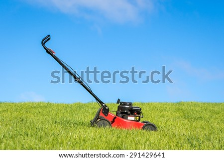 Lawn mower in green grass - stock photo