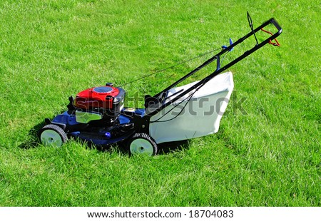lawn mower in the yard with green grass - stock photo