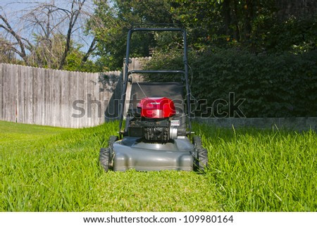 Lawn mower on cut grass path in yard