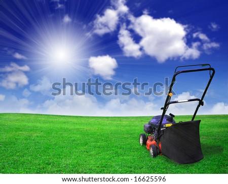 Lawn mower on green field - stock photo