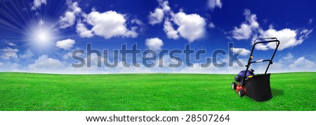 Lawn mower on green field - stock photo