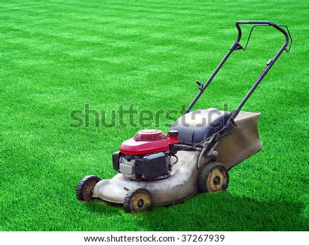 lawn mower on green grass backyard - stock photo