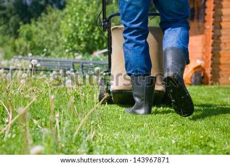 Lawn mower on the grass background. - stock photo
