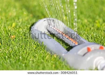 Lawn sprinkler spaying water over green grass. Irrigation system.  - stock photo