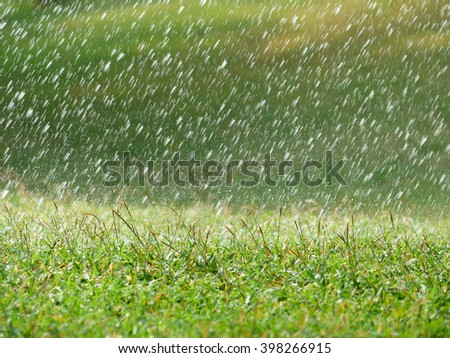Lawn sprinkler spaying water over green grass. Irrigation system. backlight, shallow depth of field, blurred bokeh sun effect - stock photo